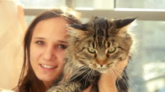 Beautiful young woman holding big Maine Coon cat in slowmotion sitting by the - stock footage
