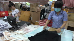 Women pack shirts for export in a Vietnamese textile company Stock Footage