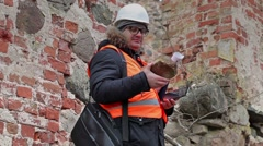 Building inspector checking brick at old ruins Stock Footage