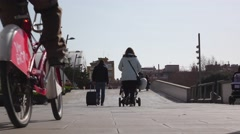 People walk and ride along pedestrian passage, low perspective shot Stock Footage