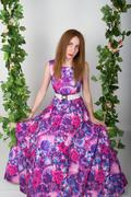 Beautiful young leggy redhaired woman in a long colorful dress on a swing - stock photo
