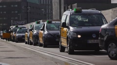 Taxi queue being move towards, telephoto view, black-yellow Barcelona cabs line Stock Footage