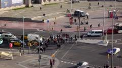 Pedestrians cross Avenida del Parallel at Plaza de Espanya, telephoto view Stock Footage