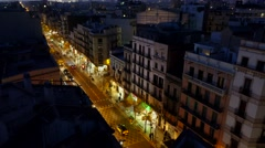 Barcelona street from top at night, dark buildings, illuminated roadway Stock Footage