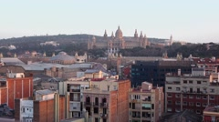 Montjuic hill and National Palace highlight by low evening sun, rooftops view Stock Footage