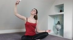 Girl in lotus position making selfie Stock Footage