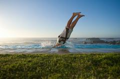 Stock Photo of Man diving into infinity pool