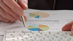 Businessman's hand showing diagram on report with pen. Stock Footage