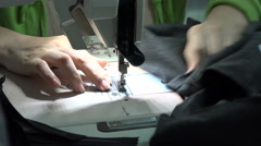 Poorly lit clothing factory, man works on production line, sewing machine, Asia Stock Footage