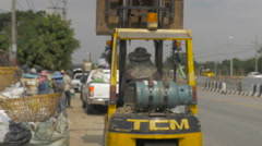 A forklift arrives at a busy recycling center with it's lift up - stock footage