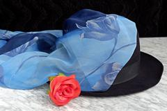 Black hat with a blue scarf with the motif of roses red rose on a marble tabl - stock photo