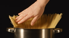 A cook touches a bunch of a spaghetti in a steel pot Stock Footage