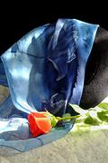 Black hat with a blue scarf with the motif of roses red rose on a marble tabl Stock Photos