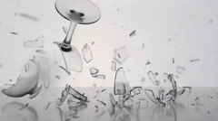 Clear winegalss falls and breaks on a white table Stock Footage