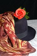 Black hat with a scarf with a tiger motif of red rose on a marble table, fash - stock photo