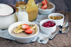 Bowl of multigrain porridge with baked bananas and strawberries Stock Photos