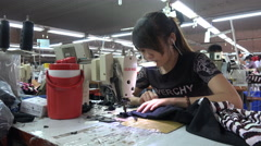 Young woman listens to music in earphones in a garment factory in Vietnam - stock footage
