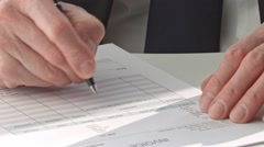 Male hand in suit filling in invoice paper Stock Footage
