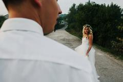 bride leads groom on the road - stock photo