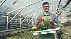 Smiling man holding pot with flowers in a garden center. RAW video record Stock Footage