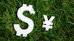 Exchange rate. The yen and the dollar sign on grass. - stock photo