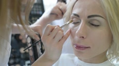 Make up artist and hair dresser work with beautiful blonde woman model - stock footage