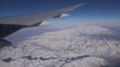 Wing of Aeroflot plane flying over Winter mountain landscape Afghanistan Stock Footage