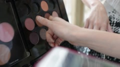 Shelf with cosmetics - lipstick, eye shadow and pencils in a beauty salon - stock footage
