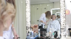 Make up artist and hair dresser work with beautiful blonde woman model Stock Footage