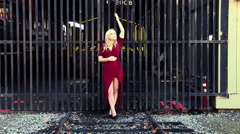 Stock Video Footage of Woman Red Dress Posing While Holding On To Gate