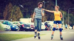 Young couple on roller skates riding outdoors - stock photo