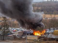 Accident dangerous fire with dark black and grey smoke at car service station Stock Photos