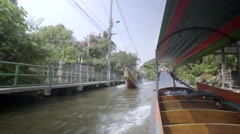 Traditional khlong boat makes its way along one of the city's many canals - stock footage