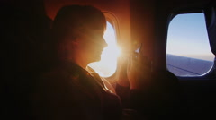 Young woman on board the aircraft writes sms outside beautiful sunrise Stock Footage
