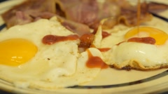 Fried Eggs & Bacon, Tomato Ketchup Being Poured Over Eggs Close Up Stock Footage