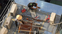 A Vietnamese welder at work on a rooftop, construction site in Saigon (HCMC) - stock footage