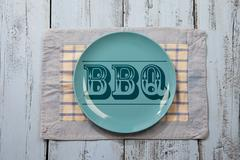 Empty plate with BBQ icon on light blue wooden background Stock Photos