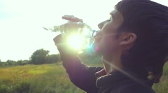 Cross-country trail running man having water break at sunset in slowmotion Stock Footage