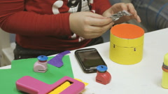 Little girl makes crafts toys from cardboard Stock Footage
