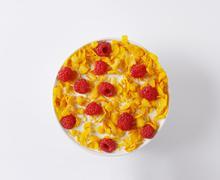 Healthy breakfast - bowl of cornflakes and raspberries in milk Stock Photos