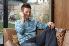 Man using a cellular telephone on sofa - stock photo