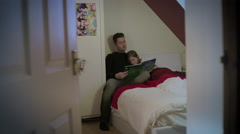 Father reads story book to young daughter in a bed in daughter's bedroom. Stock Footage