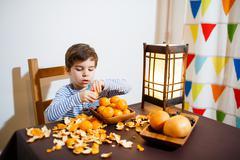 Four years boy eat a mandarin Stock Photos