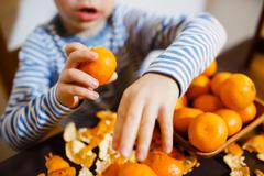 Four years boy eat a mandarin - stock photo