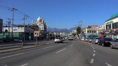Road traffic in Downtown of Sokcho with Seorak Mountains at background Stock Footage