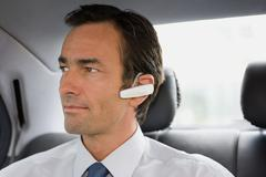 Businessman with bluetooth headset sitting in car - stock photo