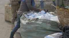 Women sort through a large bag of empty white plastic water bottles - stock footage