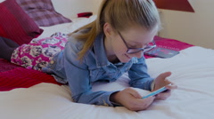Young girl wearing glasses lying on bed watching a video on her smartphone. Stock Footage