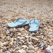 Flip flops on a shingle beach Stock Photos