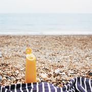 Suntan lotion on shingle beach Stock Photos